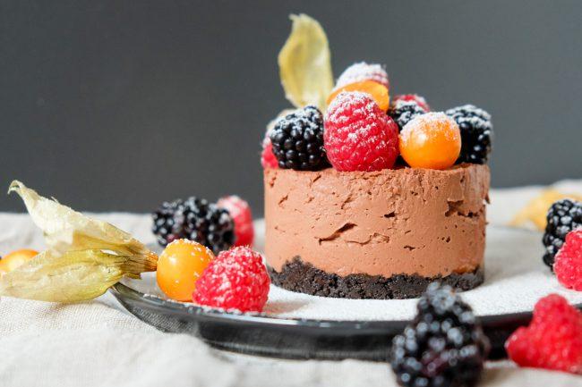 Rezept für einen no-bake Schoko-Cheesecake. Der Tortenboden wird aus Oreo-Keksen zubereitet und die Törtchen werden mit frischen Beeren dekoriert.