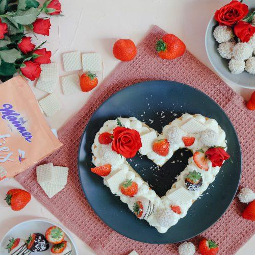 Muttertagstorte im Letter Cake Stil auf grauem Teller. Daneben befinden sich Erdbeeren, Manner Waffeln und rote Rosen
