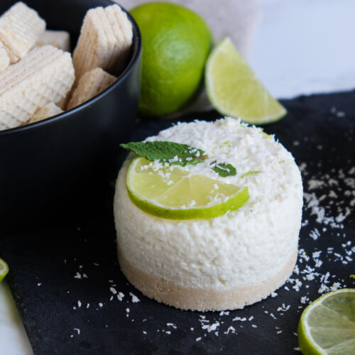 Kokos-Limetten-Törtchen dekoriert mit Limette und frischer Minze. Im Hintergrund ist eine Schale mit Manner Waffeln und Limetten