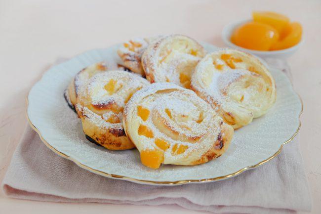 Süße Blätterteigteilchen mit Quark und Aprikosen gefüllt. Die Blätterteigteilchen liegen auf einem Teller mit Goldrand und sind mit etwas Puderzucker bestäubt. Im Hintergrund befindet sich ein kleines Schälchen mit Aprikosen.