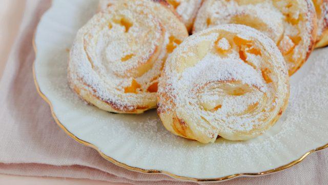 Süße Blätterteigteilchen mit Quark und Aprikosen gefüllt. Die Blätterteigteilchen liegen auf einem Teller mit Goldrand und sind mit etwas Puderzucker bestäubt.