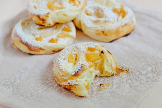 Süße Blätterteigteilchen mit Quark und Aprikosen gefüllt. Die Blätterteigteilchen liegen auf einem Leinentuch und sind mit etwas Puderzucker bestäubt. Das vordere Gebäck ist bereits angebissen.