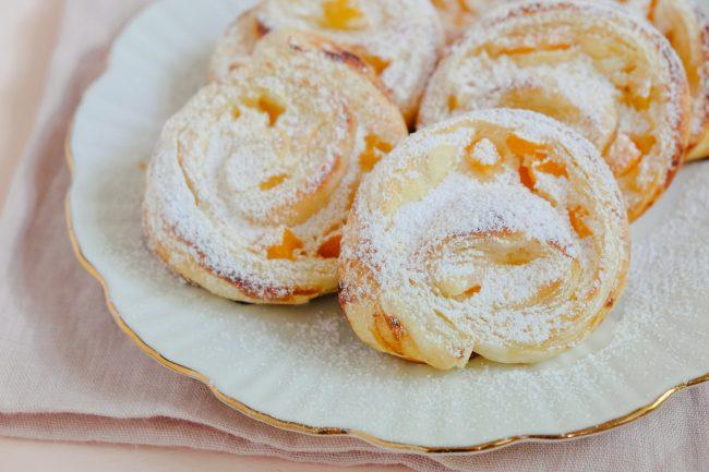 Süße Blätterteigteilchen mit Quark und Aprikosen gefüllt. Die süßen Stückle liegen auf einem weißen Teller mit Goldrand.