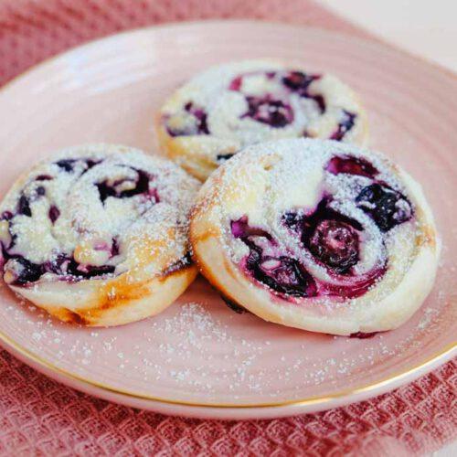 Süße Blätterteigschnecken mit Blaubeeren und Quark gefüllt auf rosanem Teller