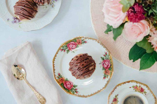 Saftiger Marmor-Muffins auf zwei verschiedenen Tellern. Daneben ist eine rosa Stoffserviette mit goldenem Löffel.