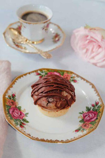 Saftiger Marmor-Muffin auf Teller. Im Hintergrund ist eine Kaffeetasse